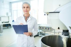 Confectionery factory worker standing with clipboard. Confectionery factory employee standing in white coat near operating machinery holding clipboard and royalty free stock images