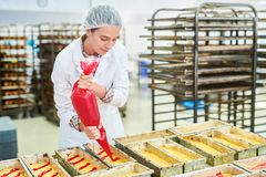 Confectionery factory employee using pastry bag. Confectionery factory worker in white coat pouring red cream from pastry bag royalty free stock image