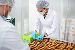 Confectionery factory employees packing ready pastry. Confectionery factory workers in white coats collecting ready pastry into box stock photography