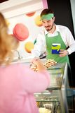 Confectionery salesman showing nice cookies. On plate stock photo
