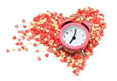 Confectionery sprinkling shape of heart with pink alarm clock Royalty Free Stock Image