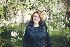 Confedent middle aged Armenian woman in a blue trench coat under the blooming tree. Confident middle aged Armenian woman in a blue trench coat and glasses under stock image
