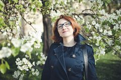 Confedent middle aged Armenian woman in a blue trench coat under the blooming tree. Confident middle aged Armenian woman in a blue trench coat and glasses under royalty free stock image