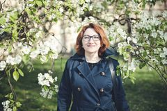 Confedent middle aged Armenian woman in a blue trench coat under the blooming tree. Confident middle aged Armenian woman in a blue trench coat and glasses under stock photos