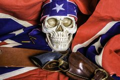 Confederate Flag and Human Skull. Human skull with confederate flag bandanna and leather holster with black revolver on confederate flag Royalty Free Stock Photo
