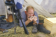 Confederate participant in camp scene playing mouth harp during recreation of Battle of Manassas, marking the beginning of the Civ Royalty Free Stock Images