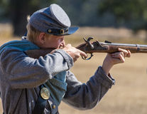 Confederate Soldier Takes Aim. A young Confederate soldier takes aim at the Union   during  a Civil War  reenactment at Hawes Farm in Anderson, California on Stock Photography