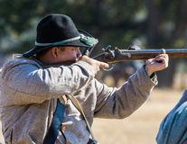 Confederate Soldier Takes Aim. A young Confederate soldier takes aim at the Union   during  a Civil War  reenactment at Hawes Farm in Anderson, California on Royalty Free Stock Photos