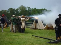 Confederate Soldiers Firing Their Muskets. Photo of a line of confederate soldiers firing their muskets at the manassas battlefield in virginia on 7/17/10.  This Royalty Free Stock Image