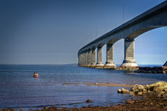 Confederation Bridge, PEI, Canada. A couple of swimmers brave the cold water by the Confederation Bridge that links Prince Edward Island and New Brunswick Royalty Free Stock Photo