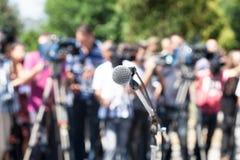 Conferência de imprensa Microfone no foco, operadores borrados da câmera fotos de stock