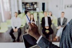 Conferência de negócio Reunião de negócio Feche acima das mãos afro do homem de negócio com a bandeja que apresenta executivos no imagens de stock royalty free