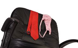 Conference. Red men's necktie and lady's bra draped over the back of a black office desk chair Royalty Free Stock Images