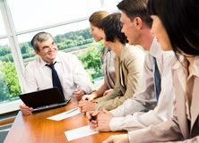 Conference. Portrait of businesspeople sitting at the table and looking at boss Stock Photos