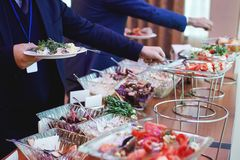 The conference banquet. The hands of people taking food with covered with greens and salads banquet table at the conference royalty free stock photos