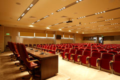 Conference center. Interior of new conference hall with red velvet chairs and presidium