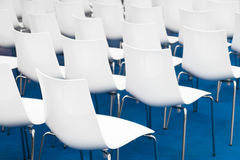 Conference chairs in business room, rows of white plastic comfortable seats in empty corporate presentation meeting office, detail Royalty Free Stock Image