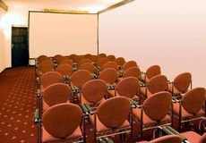 Conference hall. Several rows of red chairs in an empty  room, blank white screen in front, lots of copy space Royalty Free Stock Photo
