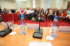 Conference in hall. bottle, microphone on table