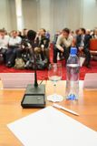 Conference in hall. focus on bottle. Royalty Free Stock Photo