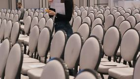 Conference hall. Rows of grey chairs. A woman numbers the seats for special guests. Mid shot stock footage