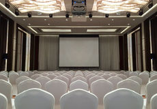 Conference Meeting Room with ceiling LED lights, Row of White Chairs, with Stage and Empty Screen for Business Meeting, Conference. Training Course, used as stock images