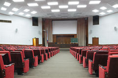 Conference room. Empty big white conference room with red armchairs Stock Image