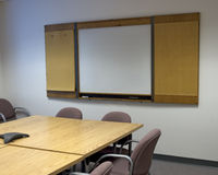 Conference room. A plain conference room, typical of a common office building. whiteboard on the wall is totally blank, text can be inserted Stock Photos