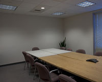 Conference room. A corner view of an empty conference room with wood, and white tables, and a conference phone Stock Photography