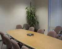 Conference room. A conference room, wth plant in the corner, and long wooden rectangular conference table, with conference phone stock images