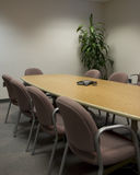 Conference room. A conference room, with long rectangular conference table and a conference phone. crop is vertical royalty free stock photography