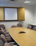 Conference Room. A vertical shot of a conference room, angled. Whiteboard, table, and conference phone royalty free stock photo