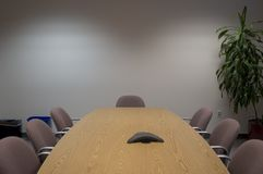 Conference room. An empty conference room with a plant in the corner and a conference phone on the table Stock Images