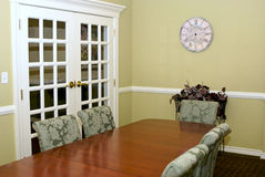 Conference Room. Fancy old fashioned meeting room showing table, chairs, french doors, flowers and clock Stock Images