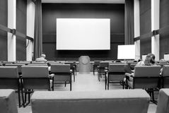 Conference room. Blank conference room projector screen from audience.Black and white conference room Stock Images