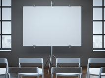 Conference room with blank screen and rows of chairs. Stock Image