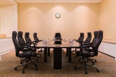 Conference room for business meetings. Large table in the middle of the room around comfortable chairs on the wall hang the clock royalty free stock photos