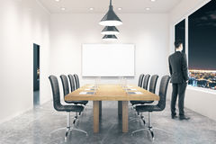 Conference room with businessman night. Conference room interior with blank board, businessman and city view at night. Mock up, 3D Rendering Royalty Free Stock Photos