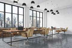 White brick meeting room corner. Conference room corner with white brick walls, a concrete floor, large windows and a long wooden table with wooden chairs near Stock Photo
