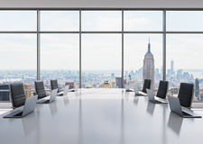 A conference room equipped by modern laptops in a modern panoramic office in New York. Black leather chairs and a white table. Royalty Free Stock Image