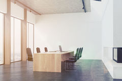 Conference room interior with a fireplace toned. Conference room interior with white walls, concrete floor, panoramic windows and a long table with laptops with Royalty Free Stock Image