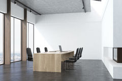 Conference room interior with a fireplace. Conference room interior with white walls, concrete floor, panoramic windows and a long table with laptops with black Royalty Free Stock Images
