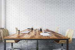 White brick meeting room interior. Conference room interior with white brick walls, a concrete floor, large windows and a long wooden table with wooden chairs Royalty Free Stock Images