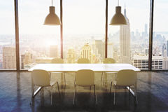 A conference room in a modern panoramic office with New York city view. White table, white chairs and two white ceiling lights. 3D Stock Photos