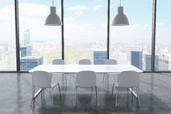 A conference room in a modern panoramic office with New York city view. White table, white chairs and two white ceiling lights. 3D Royalty Free Stock Photography
