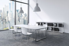 A conference room in a modern panoramic office with New York view. White table, white chairs, a bookcase and two white ceiling lig Royalty Free Stock Images