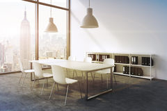 A conference room in a modern panoramic office with New York view. White table, white chairs, a bookcase and two white ceiling lig Royalty Free Stock Photo