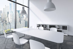 A conference room in a modern panoramic office with New York view. White table, white chairs, a bookcase and two white ceiling lig Stock Photos