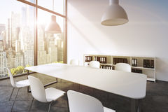 A conference room in a modern panoramic office in New York. White table, white chairs, two white ceiling lights and a bookcase. 3D Royalty Free Stock Photos