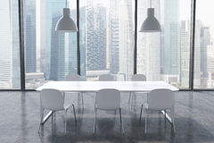 A conference room in a modern panoramic office with Singapore city view. White table, white chairs and two white ceiling lights. Stock Image